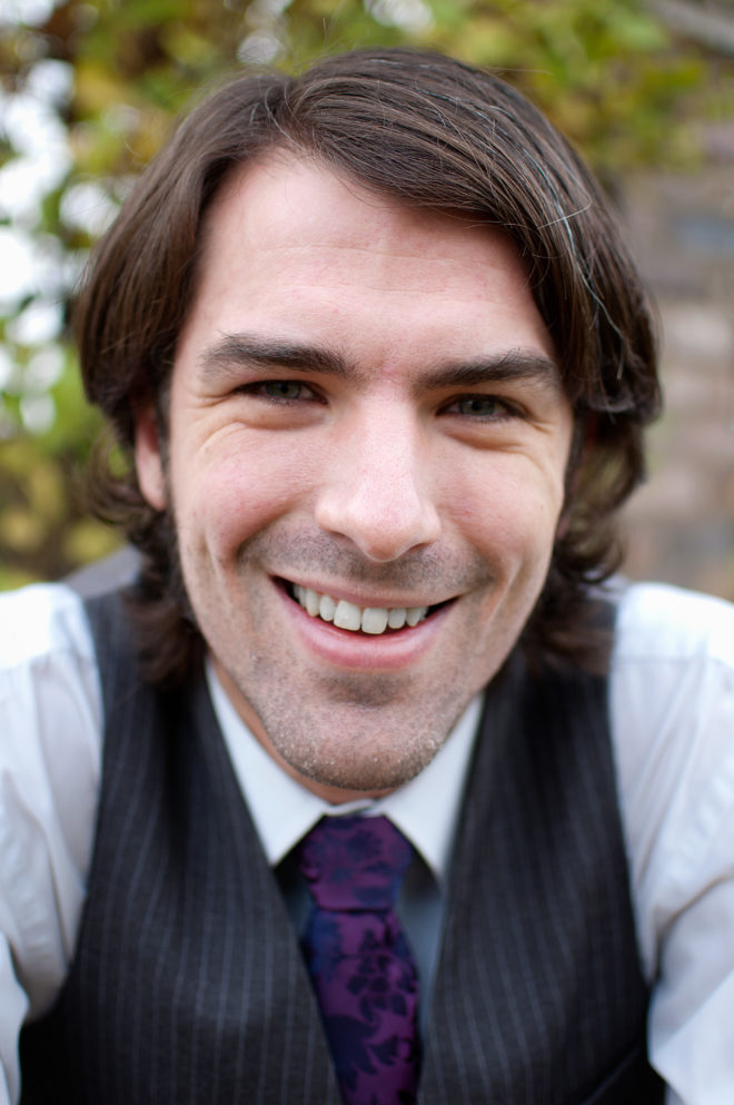 A head shot of author Matt Dovey. Matt smiles for the camera. He is wearing a grey vest, a white shirt, and a purple tie and had medium-long brown hair.