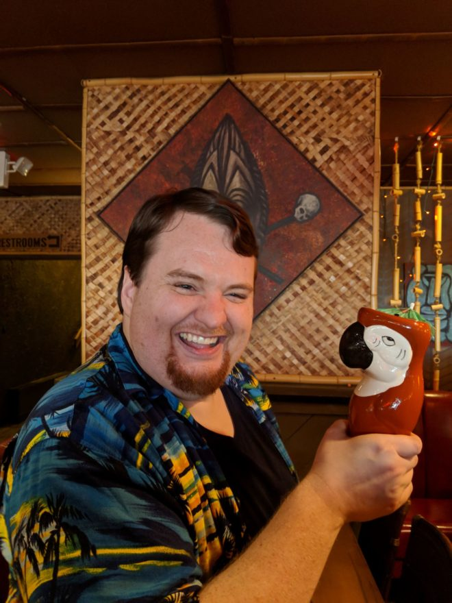 A headshot of author John Wiswell, who is wears a blue Hawaiian short and smiles for the camera. He is holding a red wooden parrot.