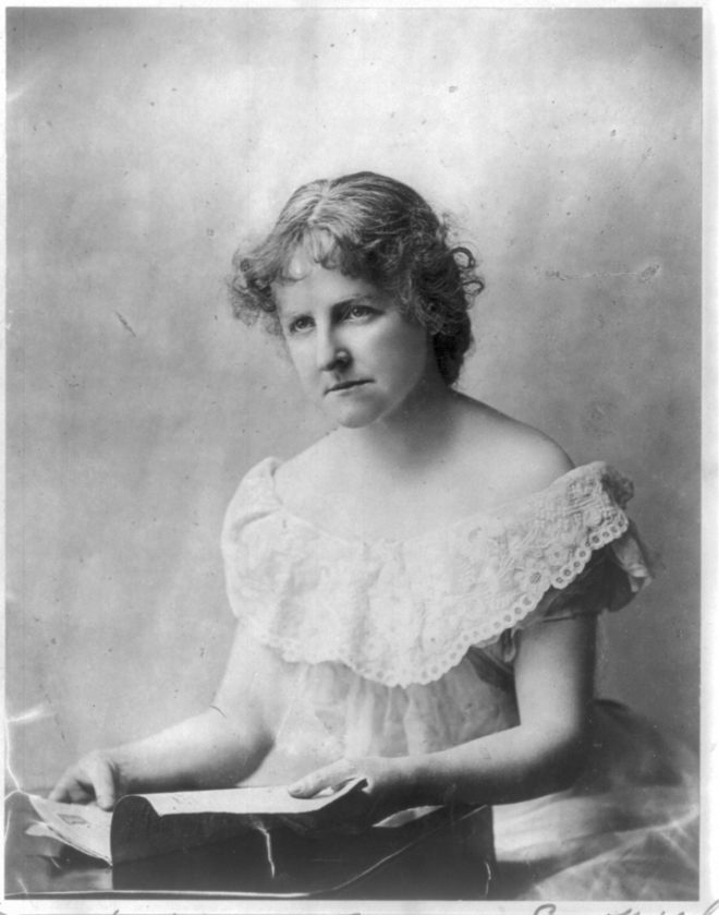 A black and white photo of Mary E. Wilkens Freeman. She is looking forward and holding a book and wearing a white lace off-the-shoulder gown.