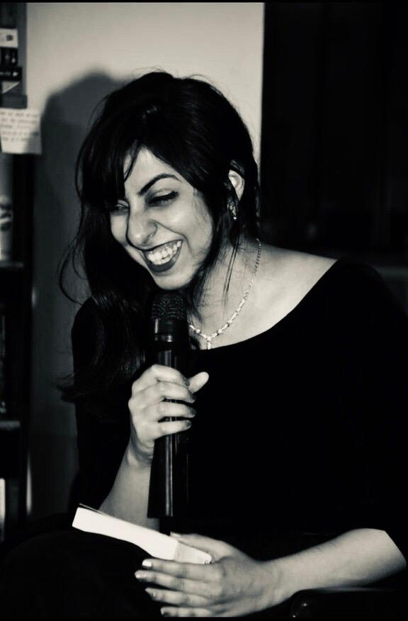 Author Damini Kane laughs and hold a microphone up to her mouth while closing her eyes. She is carrying a book and wearing a black dress.