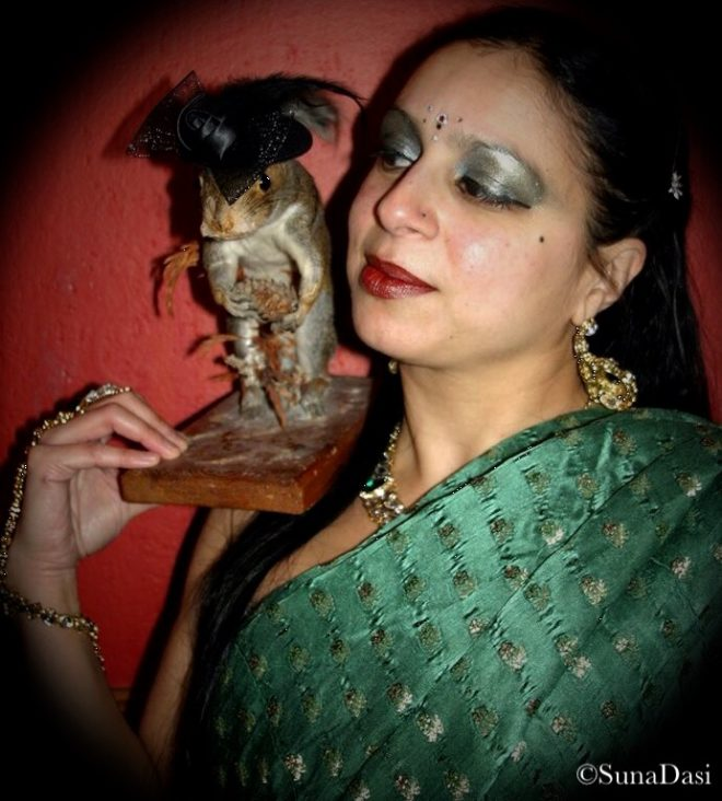 A headshot of artist Suna Dasi. She holds a taxidermied mouse statue on her shoulder. She is dressed in a green Sari and the mouse wears a black hat.